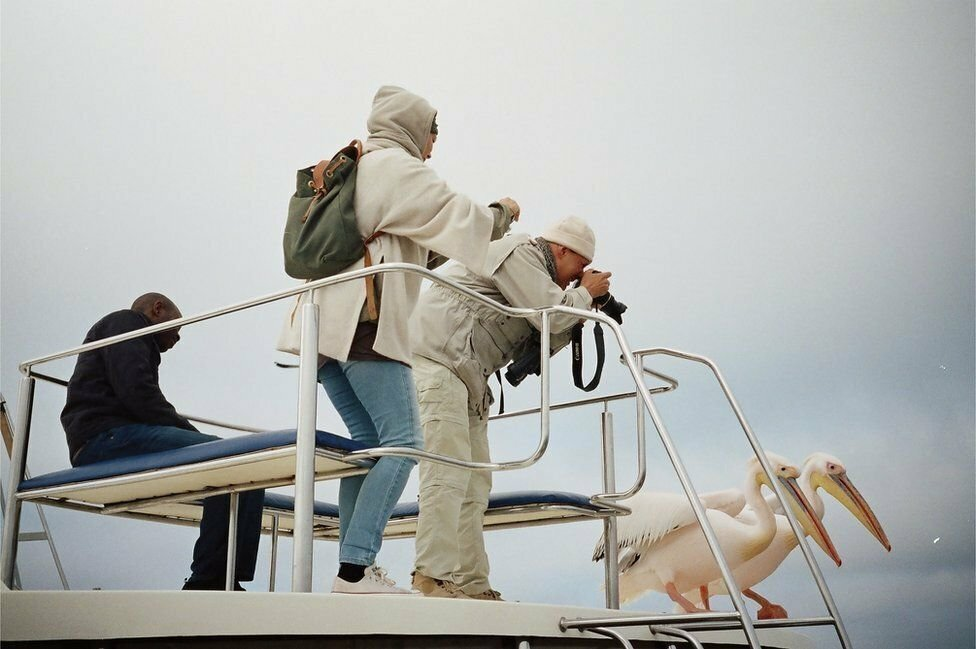 Elie Kauffmann's shot of two people taking pictures of pelicans in Namibia is shortlisted in the Open People category.