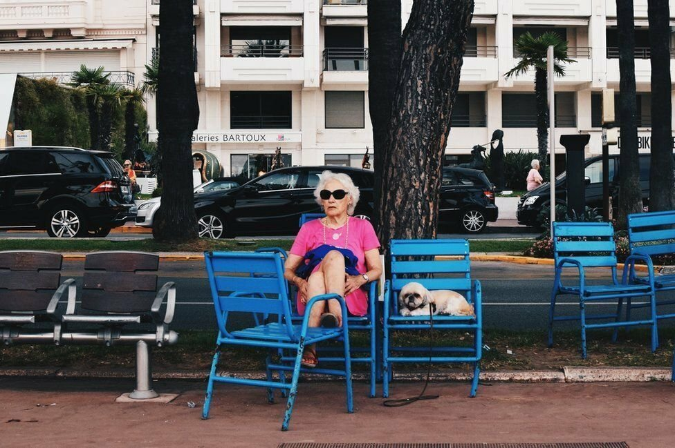 """Talia Rudofsky, competing in the Youth category, said: """"I took this photograph on Promenade de La Croisette, [Cannes,] during my summer holiday. Whilst everyone is mostly new wealth, this woman stood out, as she is relatively modest in appearance, and accompanied by a dog, as well as being elderly. I found it amusing how the dog shared the same facial expression as the woman."""""""